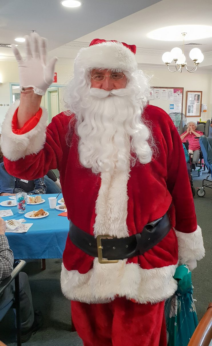 Santa visiting residents bringing candy canes and chocolates to residents at Belmont Grange